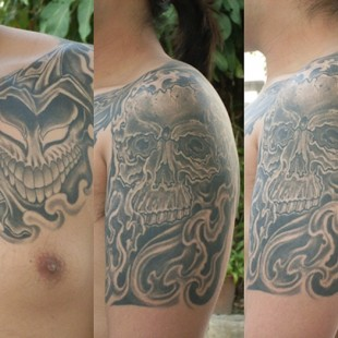 skull tattoo on shoulder and mask tattoo on chest