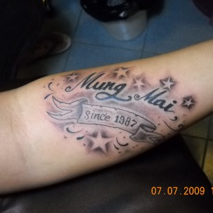 Text tattoo with detailed grey scale background with stars and banner