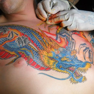 A dragon tattoo on the chest of a customer. This photo was taken while the tattoo was being done.